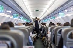Интерьер коммерчески самолета с пассажирами сервировки stewardess на местах во время полета Стоковые Фото