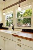 Интерьер кухни в белых тонах с верхней частью твёрдой древесины встречной Стоковые Фото