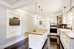 Интерьер кухни в белых тонах с верхними частями твёрдой древесины встречными Стоковое фото RF