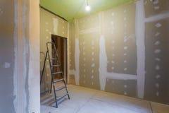 Интерьер лестницы и комнаты с гипсокартоном штукатурной плиты для стен гипса подготовленных к красить в квартире вниз стоковое изображение