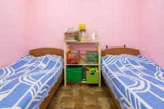 Интерьер малой комнаты общей спальни с 2 кроватями и домодельный шкаф в середине стоковая фотография rf