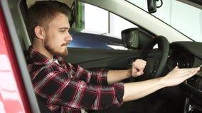 Интерьер молодого человека рассматривая нового автомобиля на салоне дилерских полномочий акции видеоматериалы