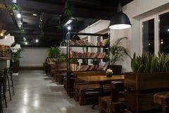 Интерьер ресторана с деревянными столами и цветками и зелеными растениями стоковая фотография rf