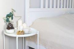 Интерьер рождества, оформление рождества на таблице около кровати Свечи, венок, подарочная коробка стоковое изображение rf