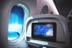Интерьер самолета с местами, окном внутри воздушного судна и экраном мультимедиа показал назначение стоковая фотография rf