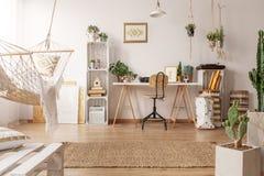 Интерьер светлой комнаты с гамаком, свежими заводами и углом домашнего офиса с деревянными столом, стулом и оформлением стоковое изображение