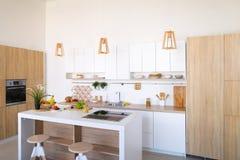 Интерьер современной светлой кухни с разнообразием приборов и стоковое изображение rf