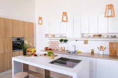 Интерьер современной светлой кухни с разнообразием приборов и стоковые фото