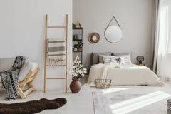 интерьер спальни открытого пространства с окном с занавесами, зеркалом и часами на стене, лестницей с одеялом, стоковая фотография