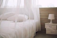 Интерьер спальни с белыми постельными принадлежностями в квартире, никто стоковые изображения
