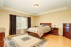 Интерьер спальни с деревянной мебелью, половиком и славными коричневыми занавесами Стоковая Фотография RF
