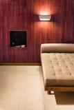 Интерьер спальни с дизайном минимализма Софа около красной деревянной стены Стоковое Изображение