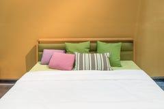Интерьер спальни с кроватью и красочной подушкой уютного дома в mo Стоковые Изображения