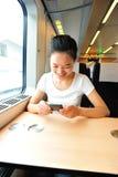 Интерьер smartphone пользы женщины поезда Стоковое Фото