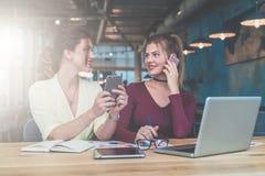 Индивидуальная встреча 2 молодых бизнес-леди сидят в офисе на таблице и работают совместно Стоковое Фото