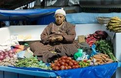 Индигенная боливийская женщина продавая овощи на рынке стоковое фото