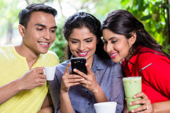 Индийская девушка показывая изображения на телефоне к друзьям стоковое изображение