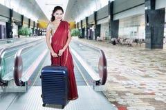 Индийская женщина держит чемодан на эскалаторе Стоковые Фото