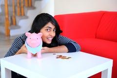 Индийская счастливая девушка с ее piggybank Стоковые Изображения RF