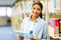 Индийская ученица колледжа читая книгу в библиотеке Стоковое Фото