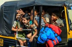 Индийские ребеята школьного возраста идя домой рикшей стоковое фото