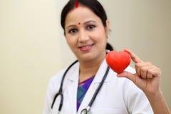 Индийский женский доктор держа красивую красную форму сердца Стоковая Фотография RF