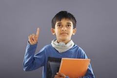 Индийский мальчик школы с учебником стоковое изображение