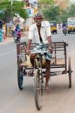 Индийский человек управляя рикшей велосипеда на толпить улице города Стоковое Изображение RF