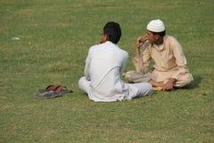 2 индийских люд ослабляя на траве Стоковая Фотография RF