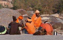 Индийское sadhus распологая на пляж около реки Ganga Стоковое Изображение