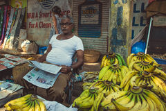 Индия, Goa - 9-ое февраля 2017: Продавец банана читает газету Стоковые Изображения