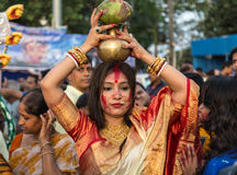 Индусская пожененная женщина держит кувшина на ее голове как часть ритуала церемонии погружения Durga Puja стоковые изображения