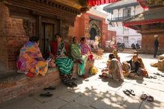 Индусские женщины в традиционном сари сидят на старом квадрате Durbar Самый большой город Непала Стоковое Изображение