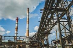 Индустриальная зона, стальные трубопроводы, облачное небо, промышленная предпосылка Стоковое фото RF