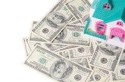 Ипотека или концепция недвижимости Небольшой дом стоя на множестве 100 долларовых банкнот изолированных на белизне Стоковые Изображения RF