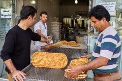 Иранские люди покупают barbari от хлебопека, Kashan flatbread, Иран Стоковое Изображение