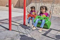 2 иранских близнеца маленьких девочек на качании, Kashan, Иране Стоковая Фотография