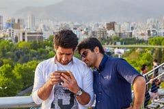 2 иранских люд просматривают изображения на экране smartphone, Tehr стоковые изображения rf