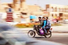 Иран, Персия, Yazd - сентябрь 2016: 3 парня идя на высокой скорости на мотоцикл на нерезкости движения предпосылки Стрельба на Стоковые Фото