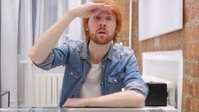 Искать жест человеком бороды Redhead сидя в офисе акции видеоматериалы
