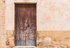Исконный коричневый деревянный парадный вход и деревенская сломленная предпосылка стены гипсолита стоковое фото