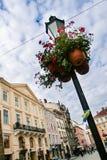 Исконный уличный фонарь с цветочными горшками против городского пейзажа стоковые фото