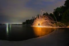 Искры от горящих стальных шерстей против фона замороженного озера Стоковое фото RF