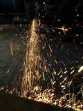 Искрящся света во время резать часть утюга в промышленной зоне стоковая фотография