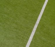 Искусственная зеленая предпосылка текстуры дерновины с белой линией метками стоковые фотографии rf