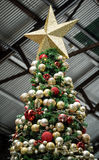 Искусственная рождественская елка с красным цветом и шариками и звездой золота Стоковые Изображения