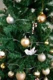 Искусственная рождественская елка украшенная с настоящими моментами underneath Стоковые Изображения RF