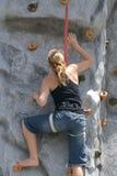 искусственний взбираясь утес девушки вверх по стене Стоковое Изображение
