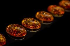 Искусственные прозрачные янтарные кабошоны на черном clo предпосылки стоковое фото rf