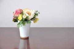 Искусственные цветки ваз на столе Стоковые Изображения
